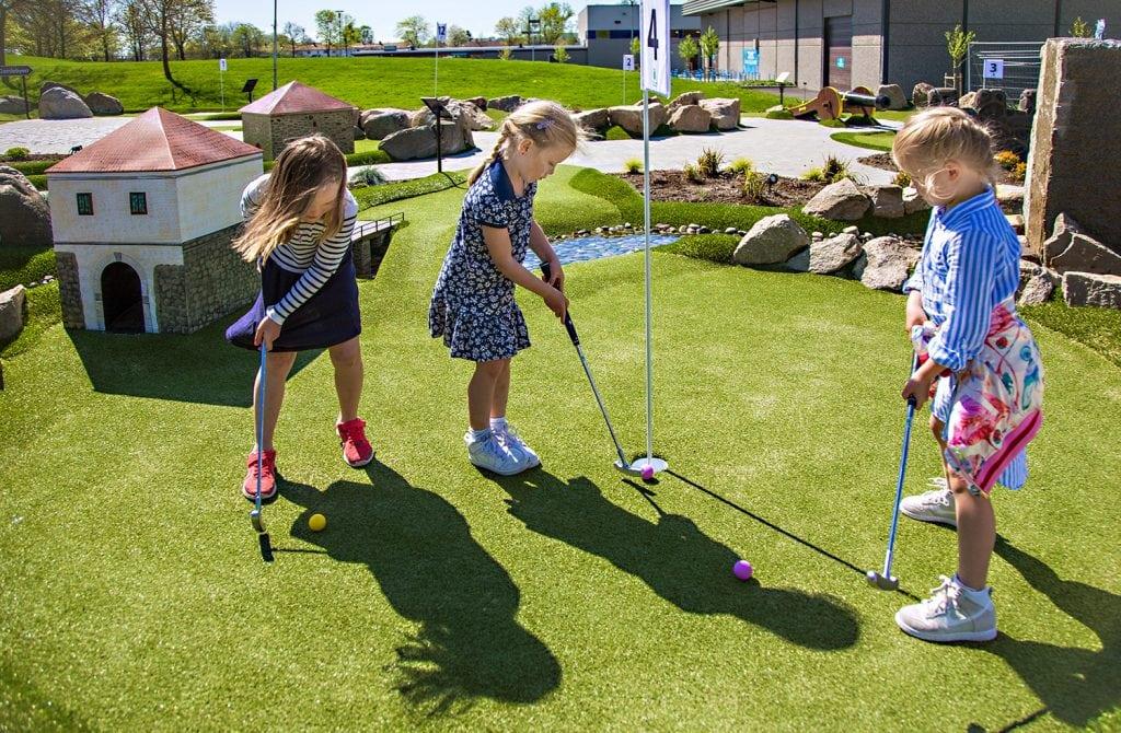 Jenter spiller minigolf i Aktivitetsbyen