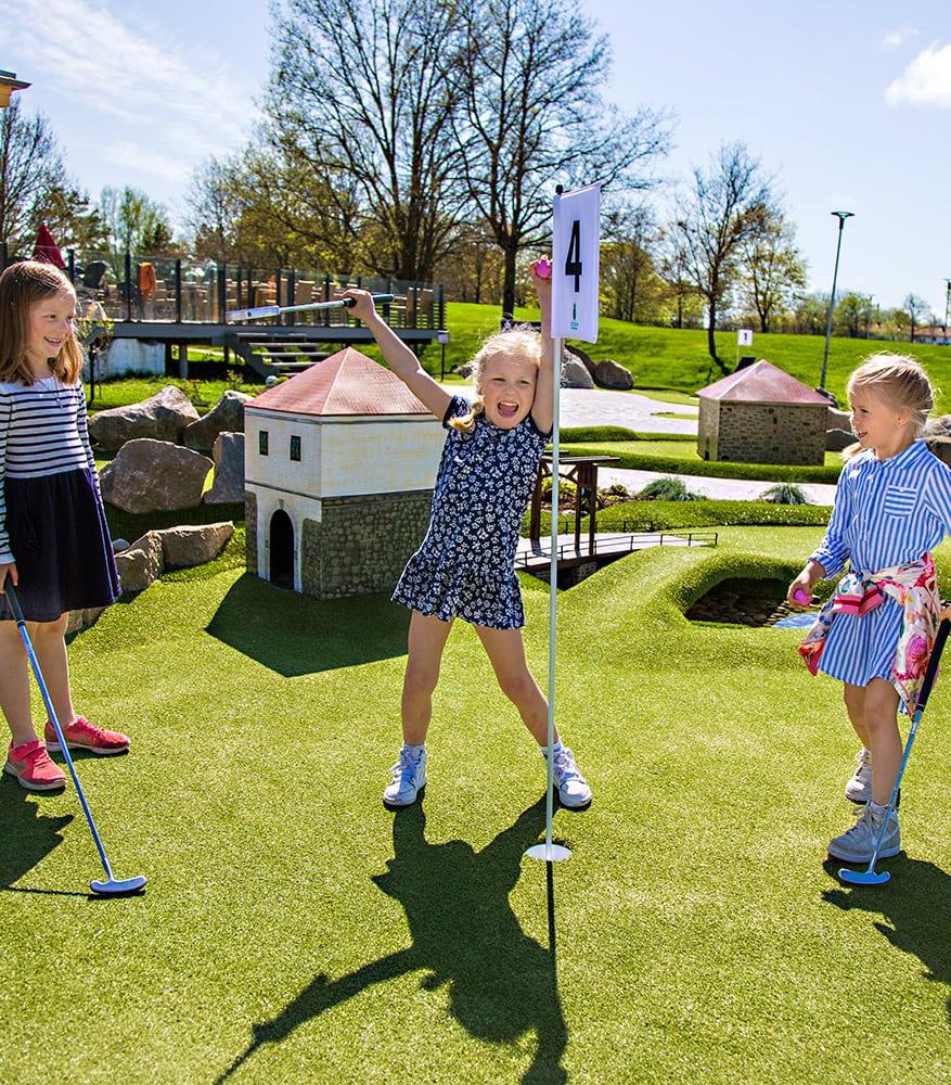 Jenter jubler og spiller minigolf i aktivitetsbyen